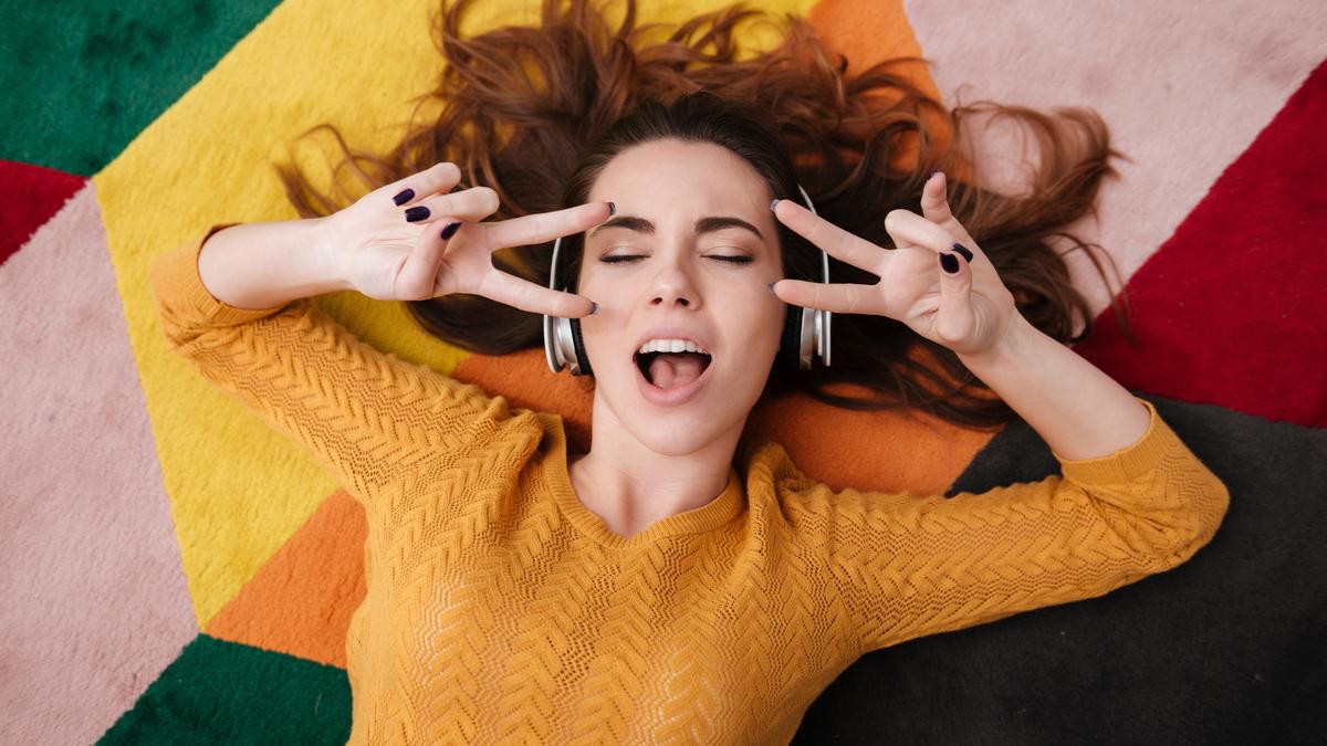 O femeie ascută muzică la căști și fredonează o melodie în timp ce stă întinsă pe covor și face semnul păcii cu ambele mâini
