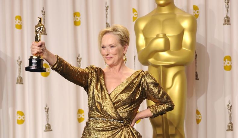 Meryl Streep, într-o rochie aurie, cu un Premiu Oscar în mână, în cadrul evenimentului organizat în 2012