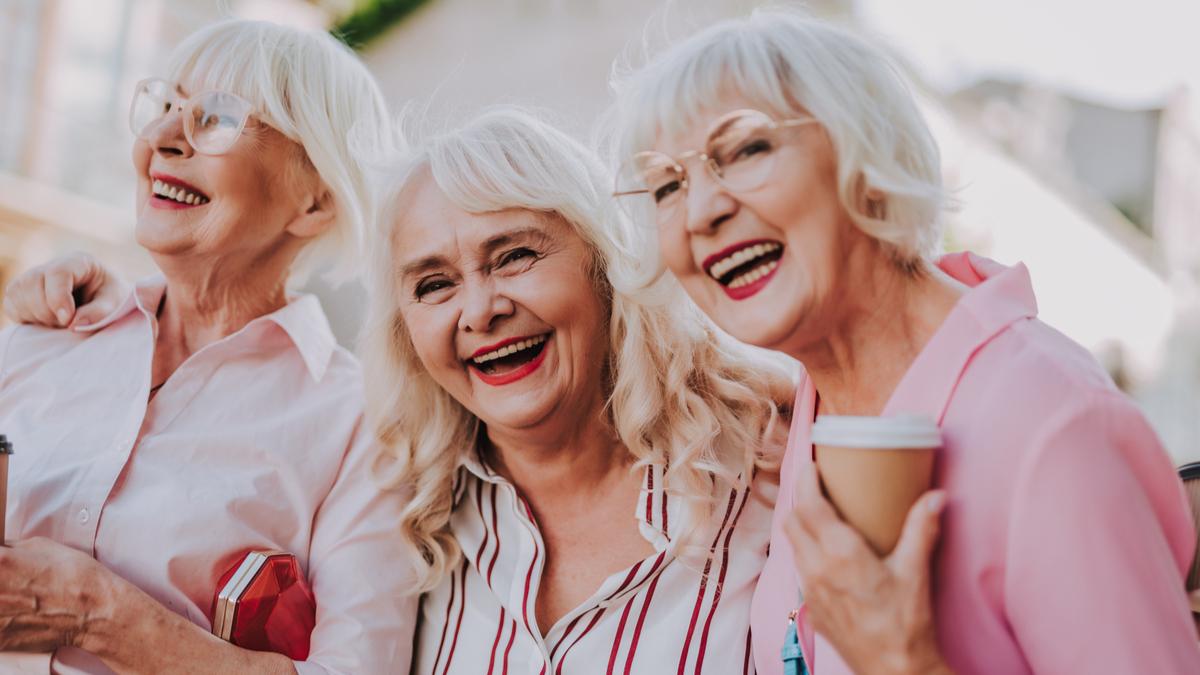 Trei femei în vârstă se îmbrățișează și râd