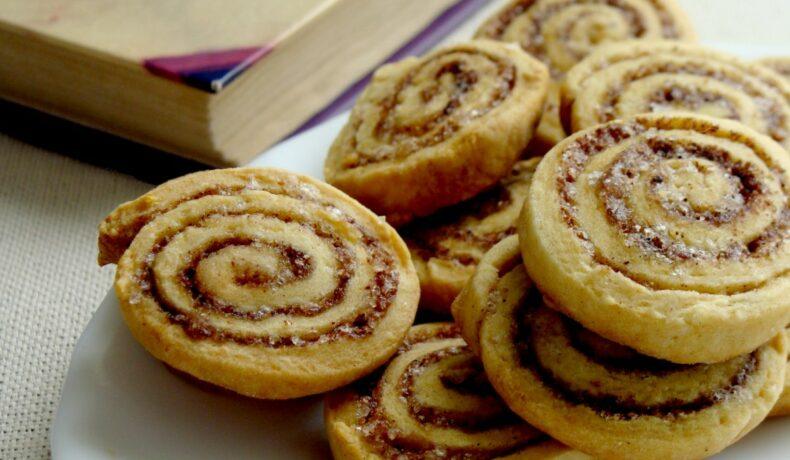 Mai multe prăjiturele tip rulou cu scorțișoară, așezate pe o farfurie albă, lângă o carte.