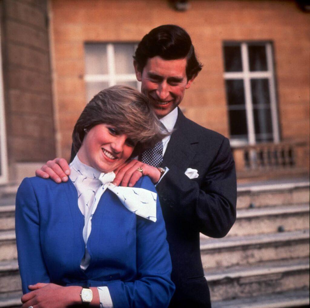 Prințul Charles îmbrăcat într-un costum negru și cravată cu buline o ține de umeri de la spate pe Prințesa Diana îmbrăcată cu un sacou albastru