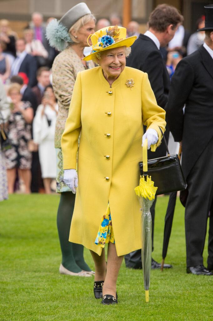 Regina Elisabeta la un eveniment public, îmbrăcată într-o ținută elegantă, galbenă