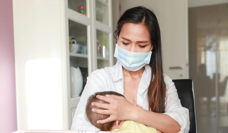 O femeie cu părul lung și șaten poartă o mască de protecție pe față și își alăptează copilul