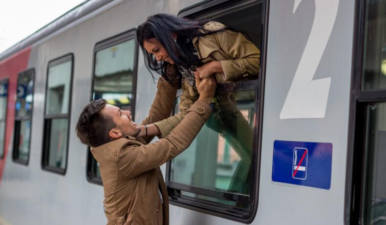O fată e apleacă pe fereastra unui tren pentru a-și îmbrățișa iubitul