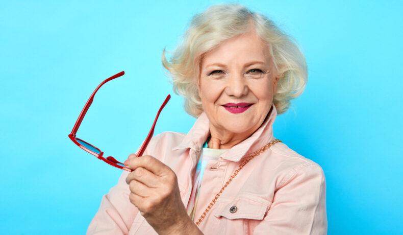 O femeie în vârstă cu părul blong, machiată și mbrcată cu o jachetă roz zâmbește la cameră și ține în mână o pereche de ochelari roșii