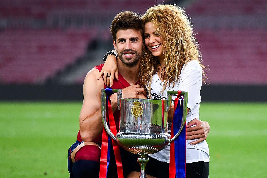 Shakira îl îmbrățișează pe Gerard Pique pe terenul de fotbal. În fața lor este o cupă de fotbal
