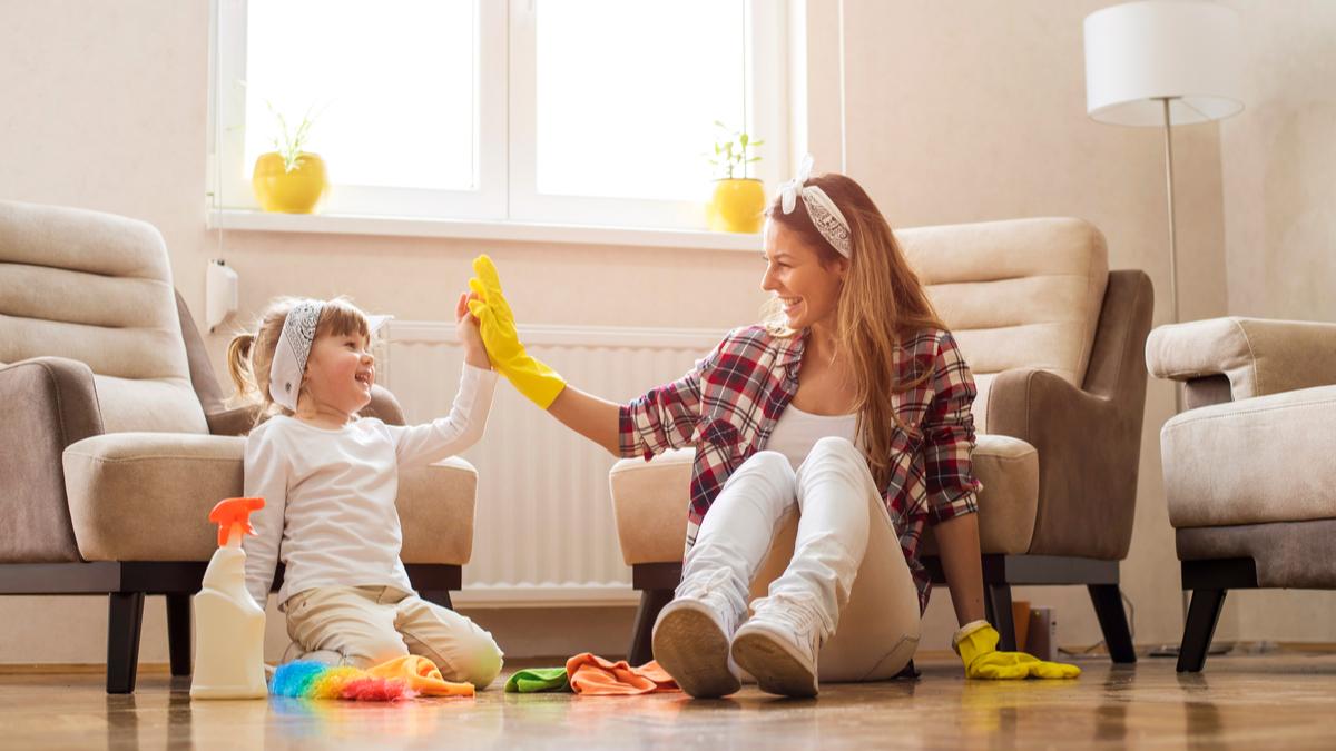 O fată și mama ei bat palma cu mănuși de menaj în mâini după ce au terminat de făcut curățenie