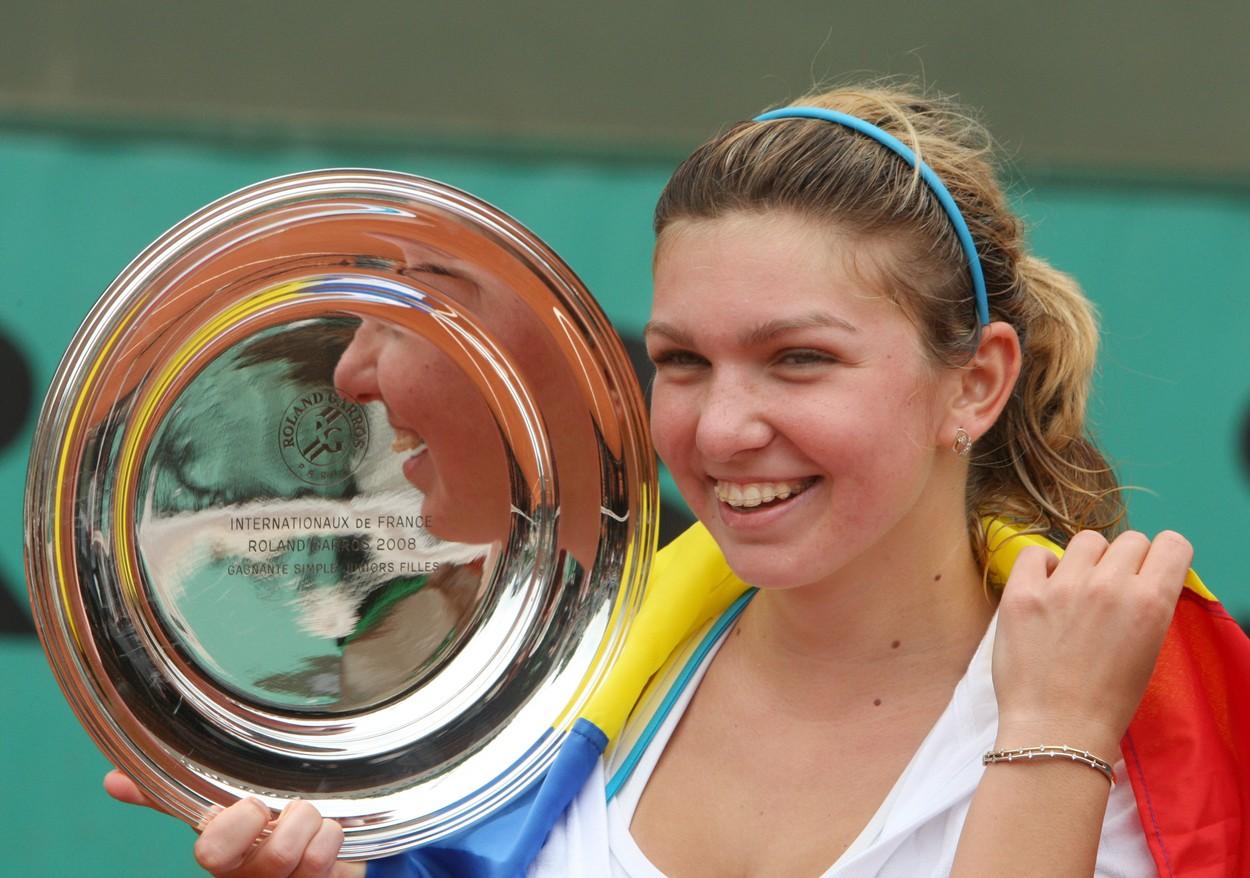 Simna Halep zâmbește pe terenul de tenis în timp ce ține în mâmă trofeul de la French Open