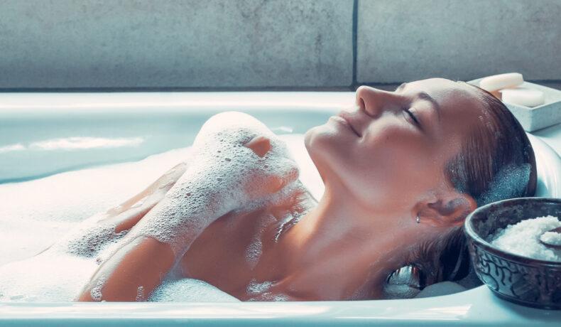 O femeie stă în cada plină cu apă acoperită de spumă