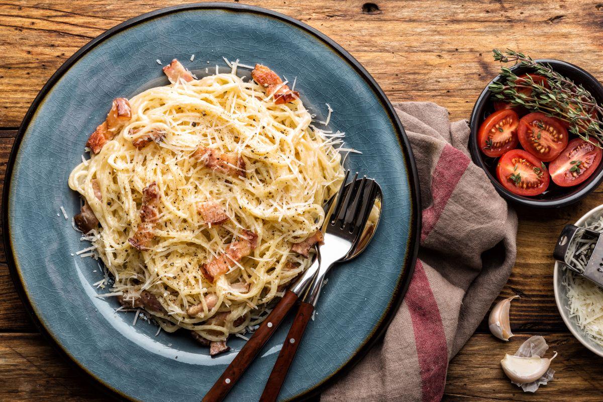 O farfurie albastră cu spaghete carbonara, pe care sunt așezate două tacâmuri. Preparatul este așezat pe o masă, alături de un prosop de bucătărie gri, câtiva căței de usturoi și un bol cu roșii tăiate și rozmarin.