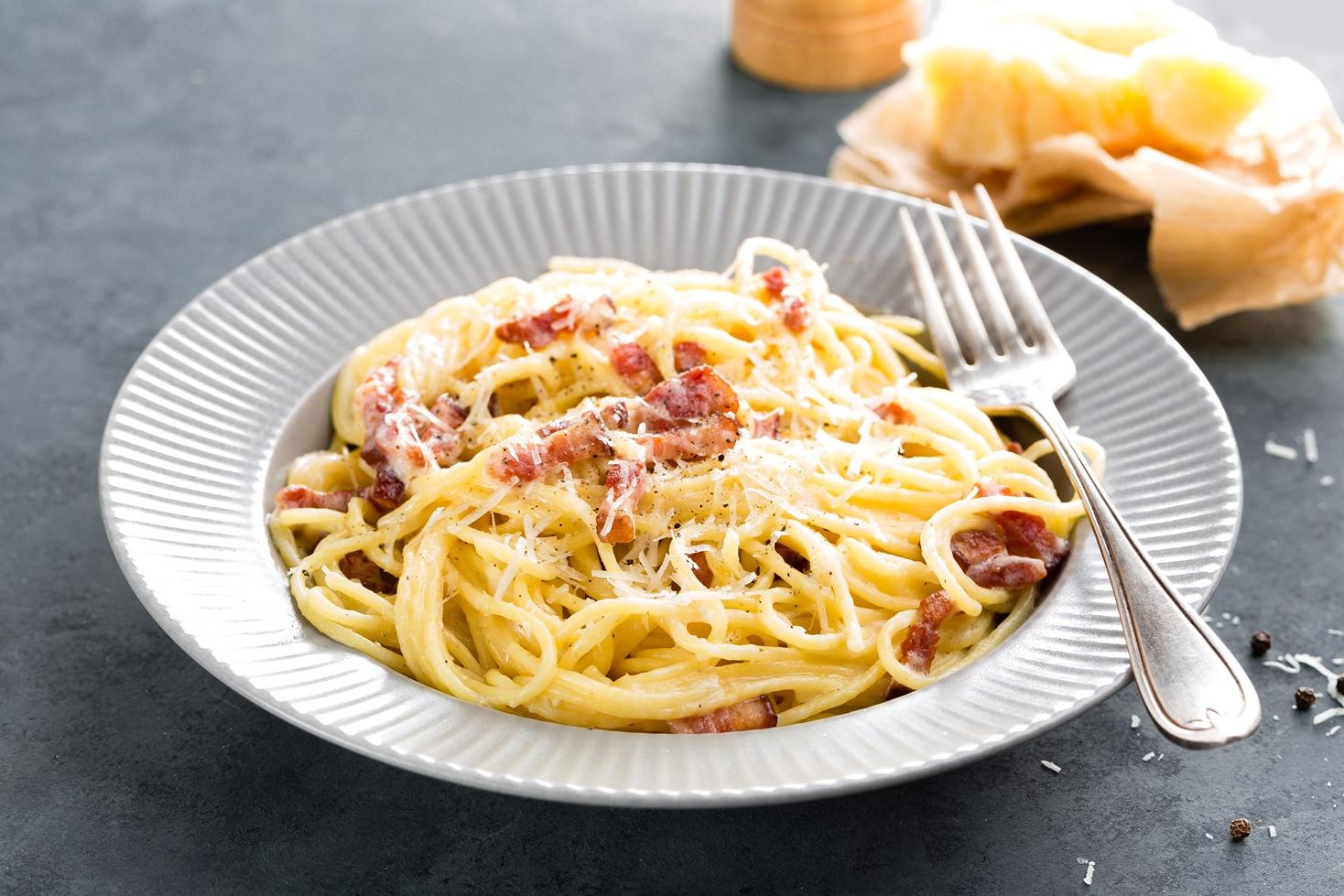 Spaghete carbonara, pe o farfurie albă, gata de sevit