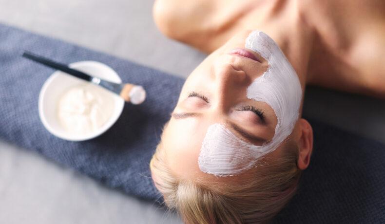 O femeie stă întinsă după ce și-a aplicat o mască facială. Lângă ea se află recipientul cu amestectul și pensulă cu care și-a întins masca