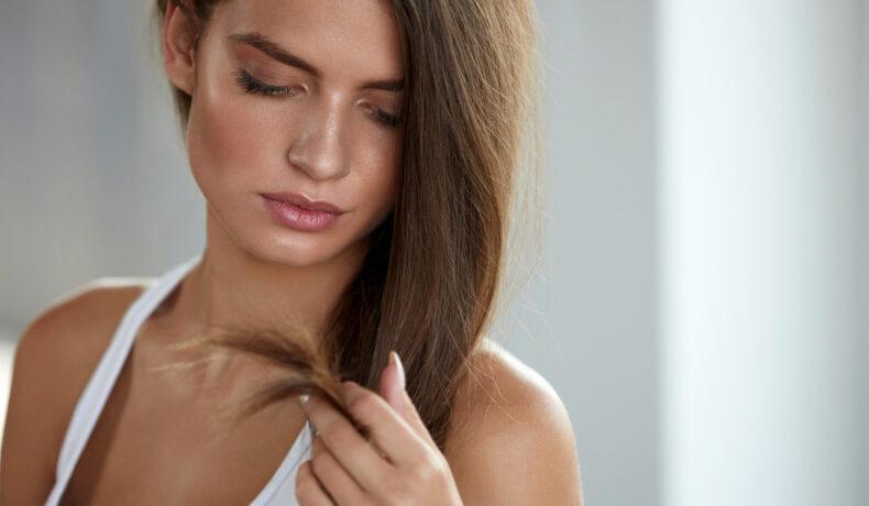 O femeie atrăgătoare cu părul lung, șaten și bogat se uită la vârfurile ei despicate