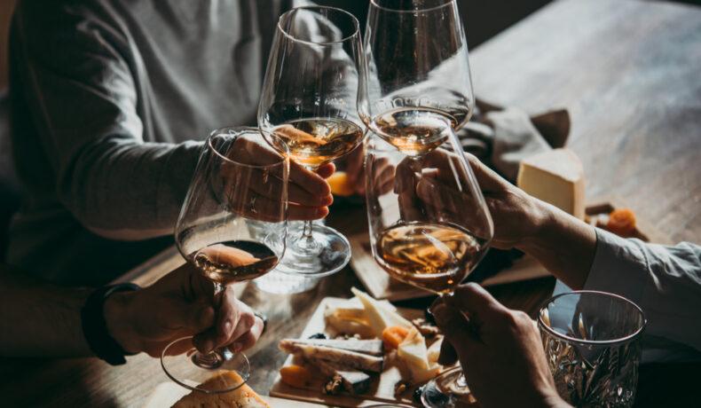 Mai multe persoae ciocnesc pahare de vin la o masă