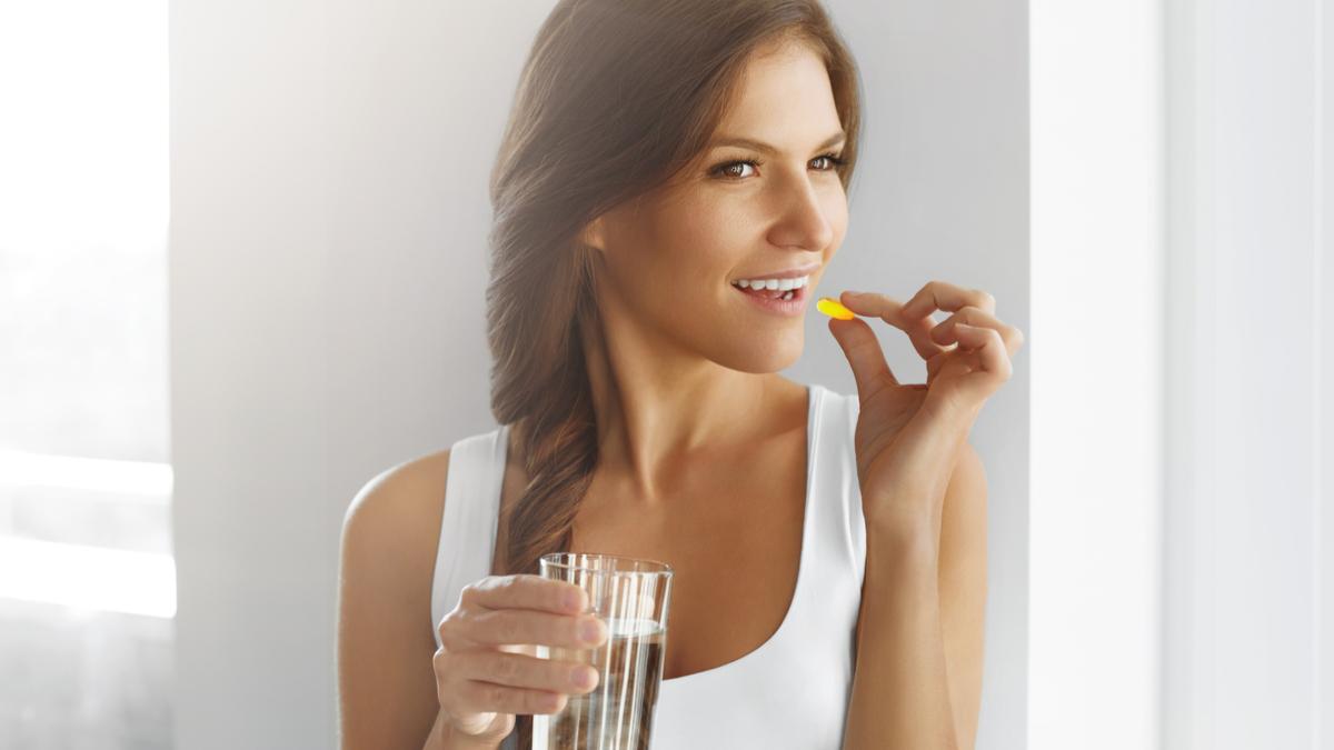 O femeie îmbrăcată cu un maieu alb ține înntr-o mână un pahar de apă în timp ce cu cealaltă mână duce la gură un supliment