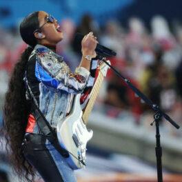 H.E.R. cântă la microfon și la chitara electrică pe scenă la Super Bowl