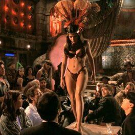 Salma Hayek pe scenă îmbrăcată într-un costum de baie maro dinn două piese și o coroană din pene pe cap