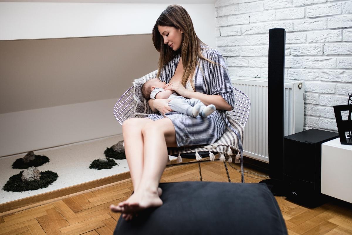 O femeie care își ține bebelușul în brațe și îl alăptează pe un scaun