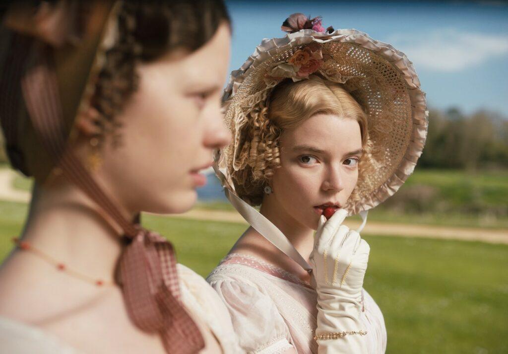 Anya Taylor Joy îmbrăcată într-un costum de epocă cu pălărie cu bor mare în producția Emma