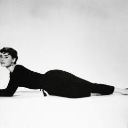 Poză alb-negru cu Audrey Hepburn încălțată cu balerini negri șă îmbrăcată într-o ținură neagră