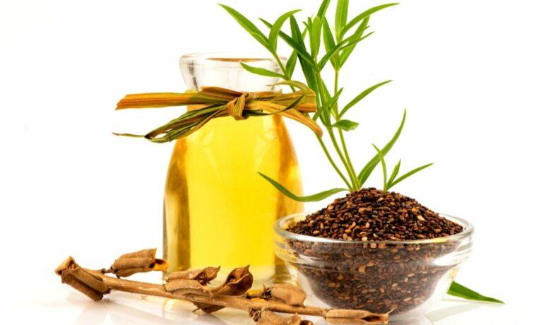 Un recipient din sticlă care conține ulei de susan și câteva frunze verzi. În fața lui se află un bol cu semințe de susan uscate.