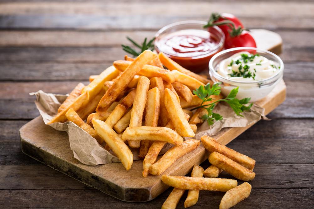 Cartofii prăjiți serviți pe un platou de lemn cu ketchup și usturoi