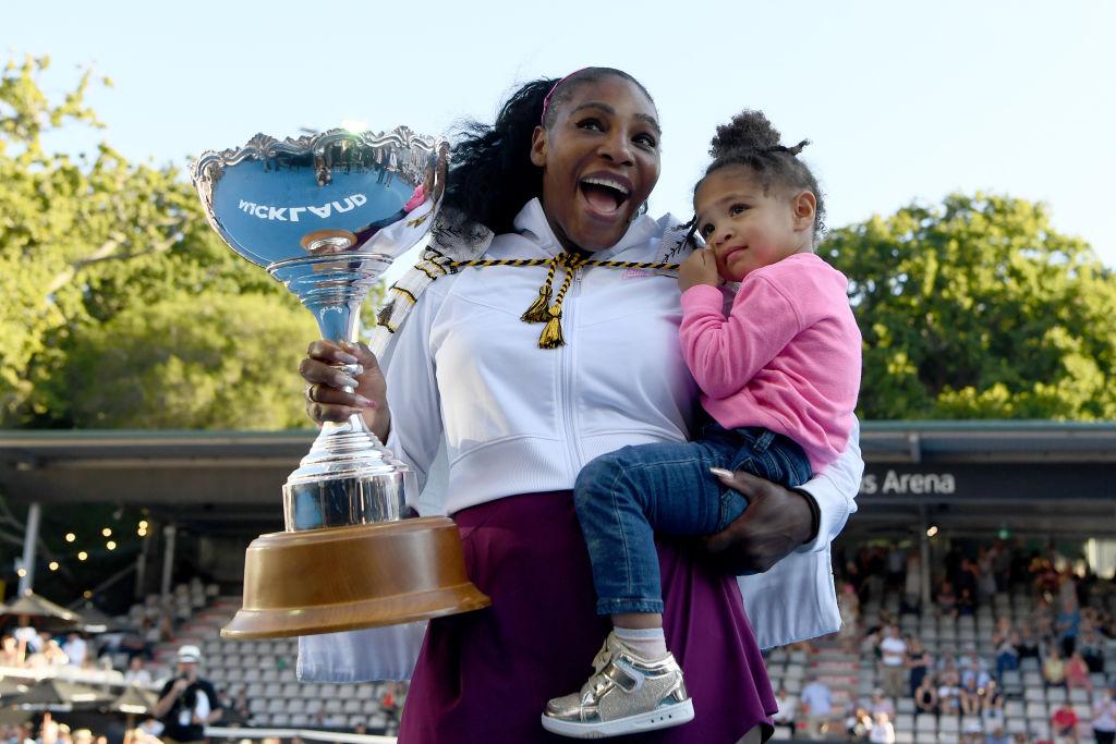 Serena Williams și fiica ei pe terenul de tenis, în timp ce ține în mână trofeul câstigat