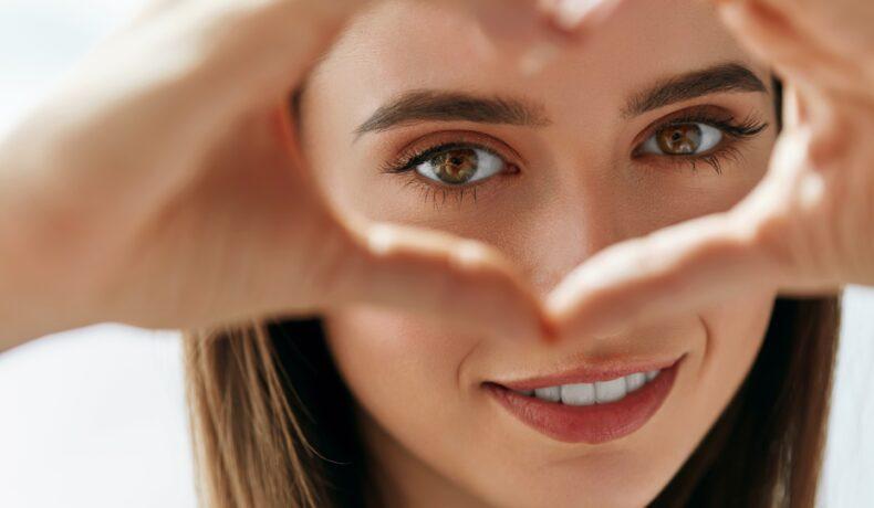 O femeie cu ochii căprui formează o inimă cu mâinile