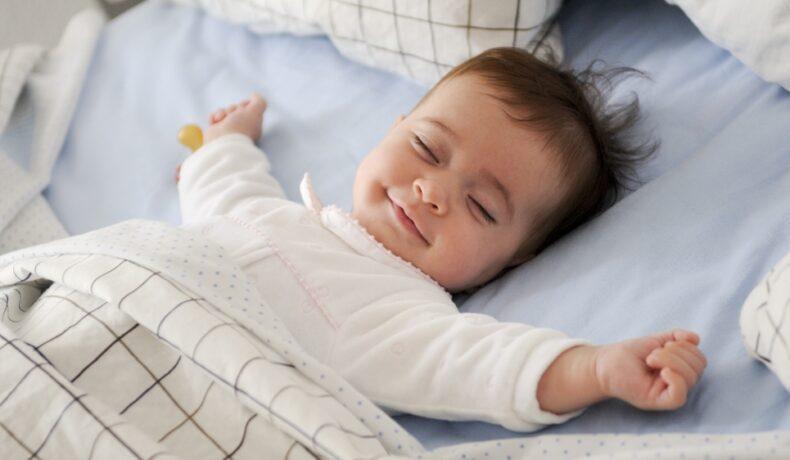 Un bebeluș zâmbește și își întinde brațele în timpul somnului