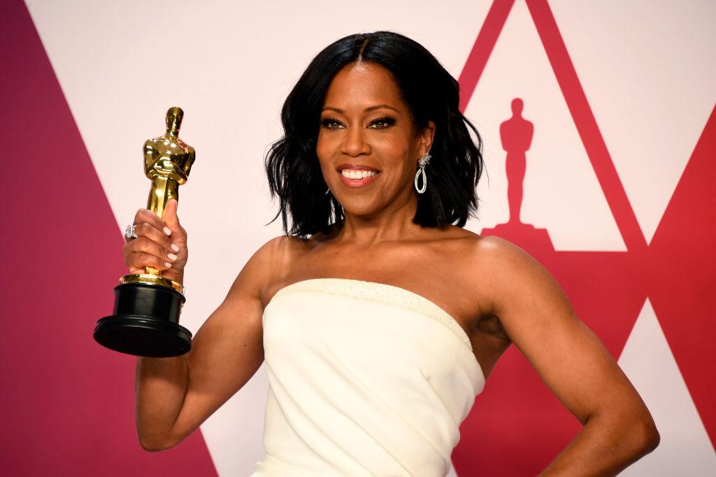Regina King pe covorul roșu la Oscar cu o statuetă în mână, îmbrăcată cu o rochie albă fără bretele