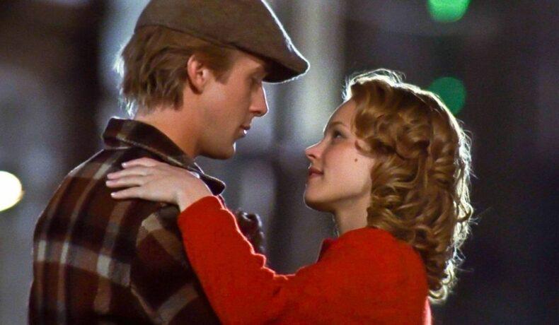 Rachel McAdams și Ryan Gosling într-o scenă romantică din filmul The Notebook. Cei doi se țin în brațe și se privesc cu multă drgoste, gata de un sărut.