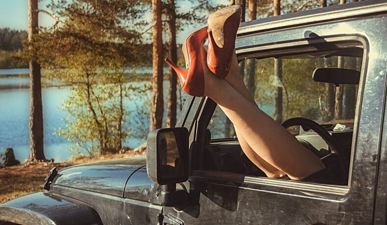 O femeie îli sprijină picioarele pe geamul unei mașini negre încălțată cu pantofi cu toc portocalii