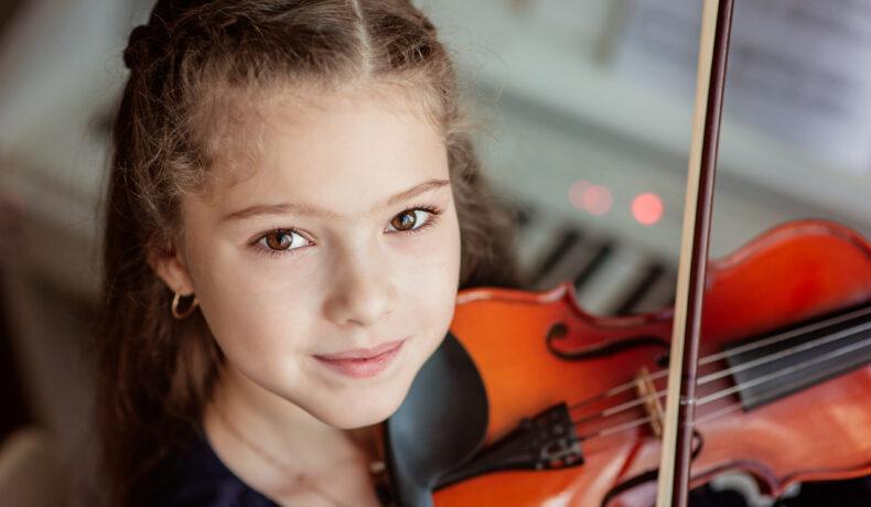 O fată cu părul lung șaten cântă la vioară