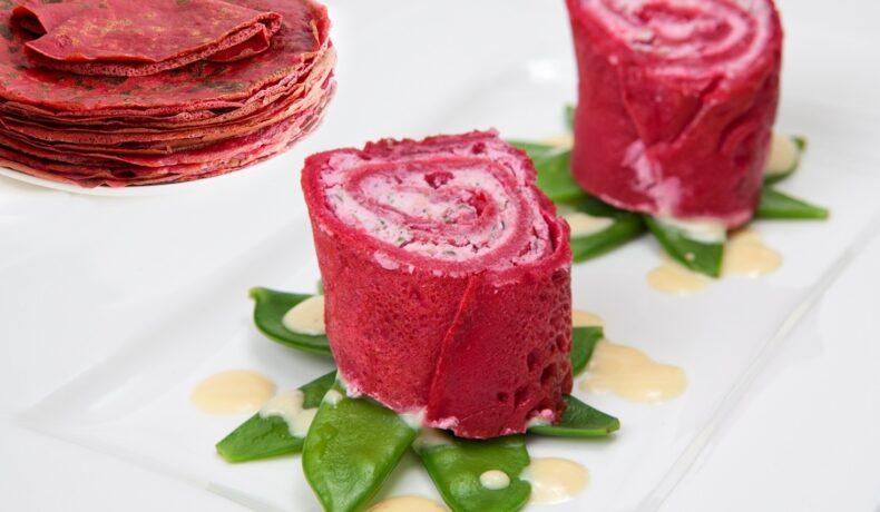 Clătite de sfeclă roșie porționate și așezate pe un platou alb, pe un pat de păstăi verzi
