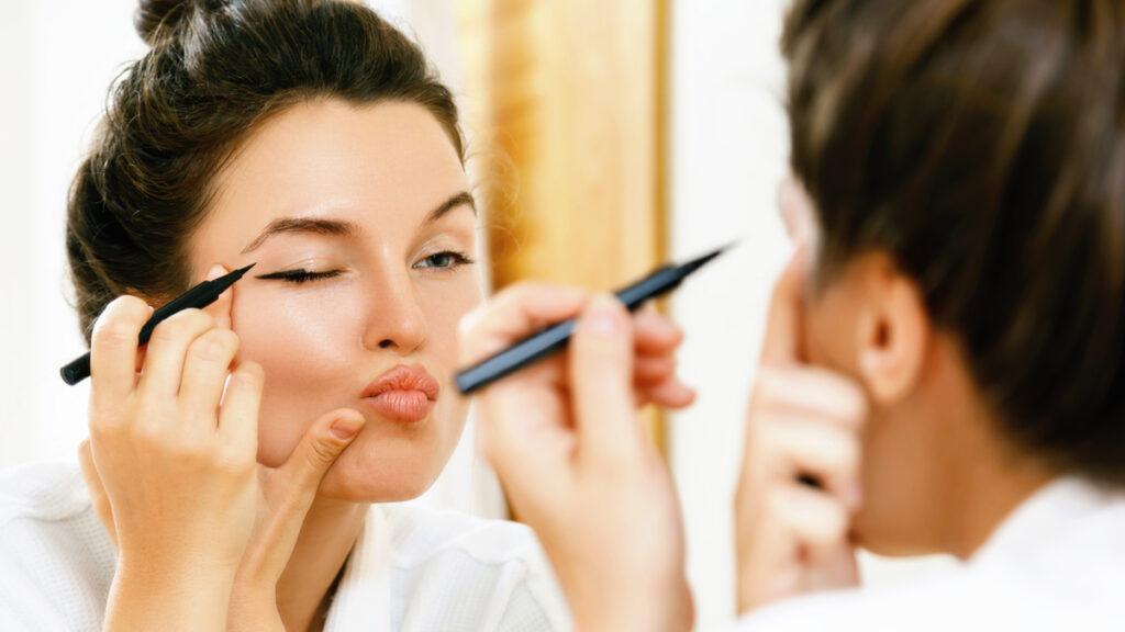 Reflexia unei femei în oglindă, în timp ce încearcă să își traseze o linie de tuș neagră