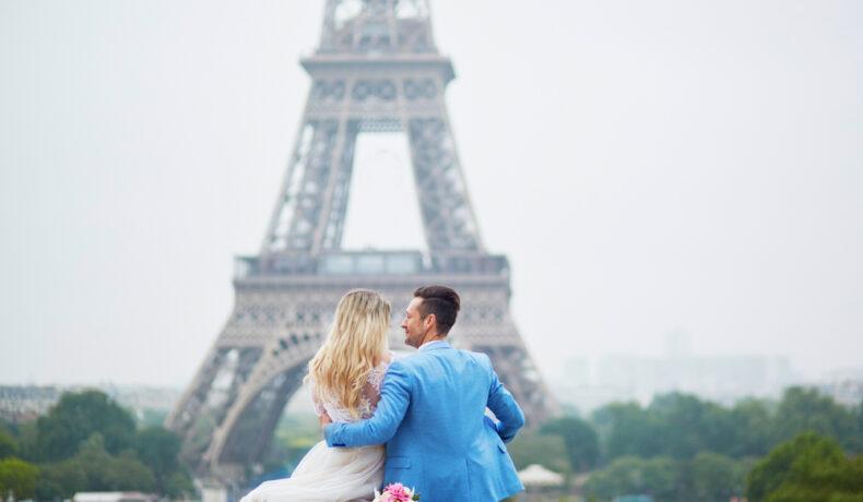 Un tânăr și iubita lui, la Turnul Eiffel din Paris, ne arată cum se sărbătorește Valentine's Day în lume