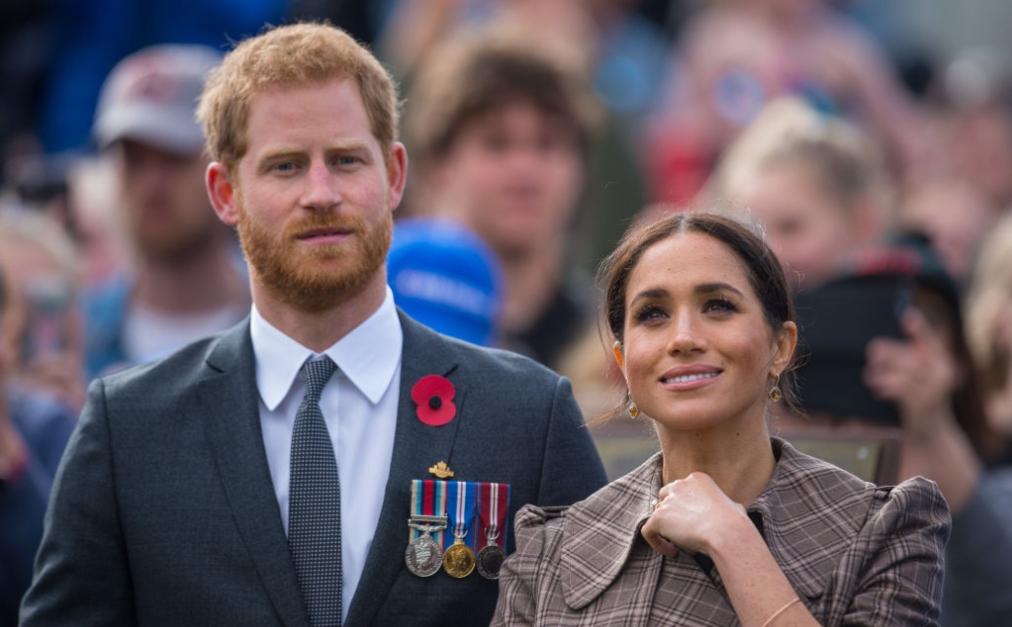 Meghan Markle îmbrăcată într-un palton maro la un eveniment alături de Prințul Harry