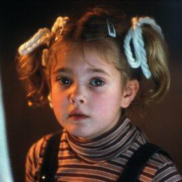 Drew Barrymore, imagine din copilărie, în care apare cu codițe și în salopetă neagră
