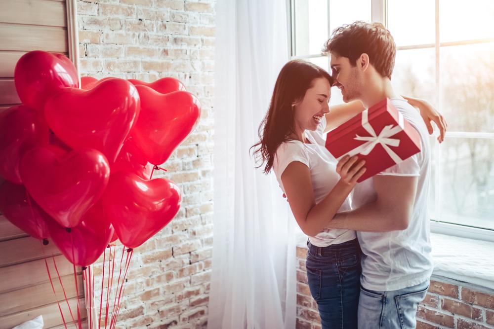 Imagine cu o cameră în care sunt baloane în care o femeie îi oferă iubitului cadoul legat de tradiții de Ziua Îndrăgostiților
