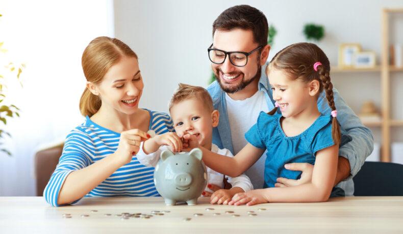 Părinți care se implică în educația financiară a copilului, la o masă cu o pușculiță