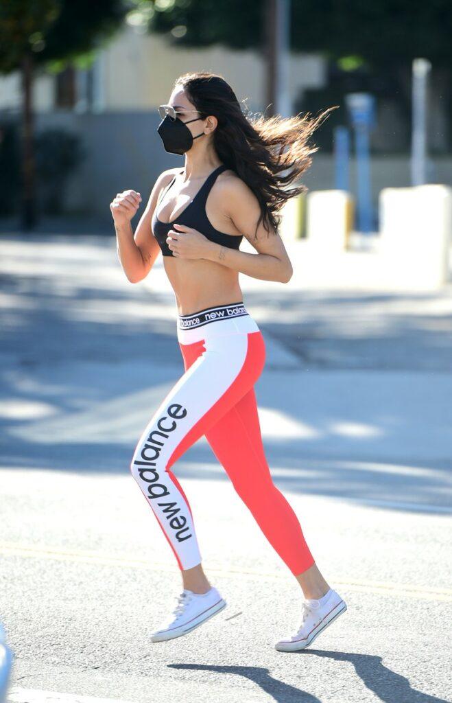 Eiza Gonzalez îmbrăcată în bustieră și colanți, în timp ce aleargă pe stradă