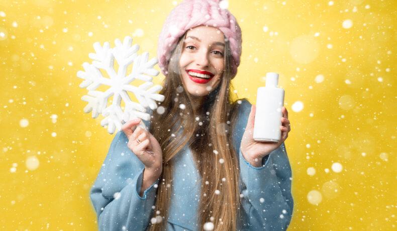 Fată șatenă cu o căciulă roz și pulover albastru pe fond galben care arată cum să-ți îngrijești părul iarna