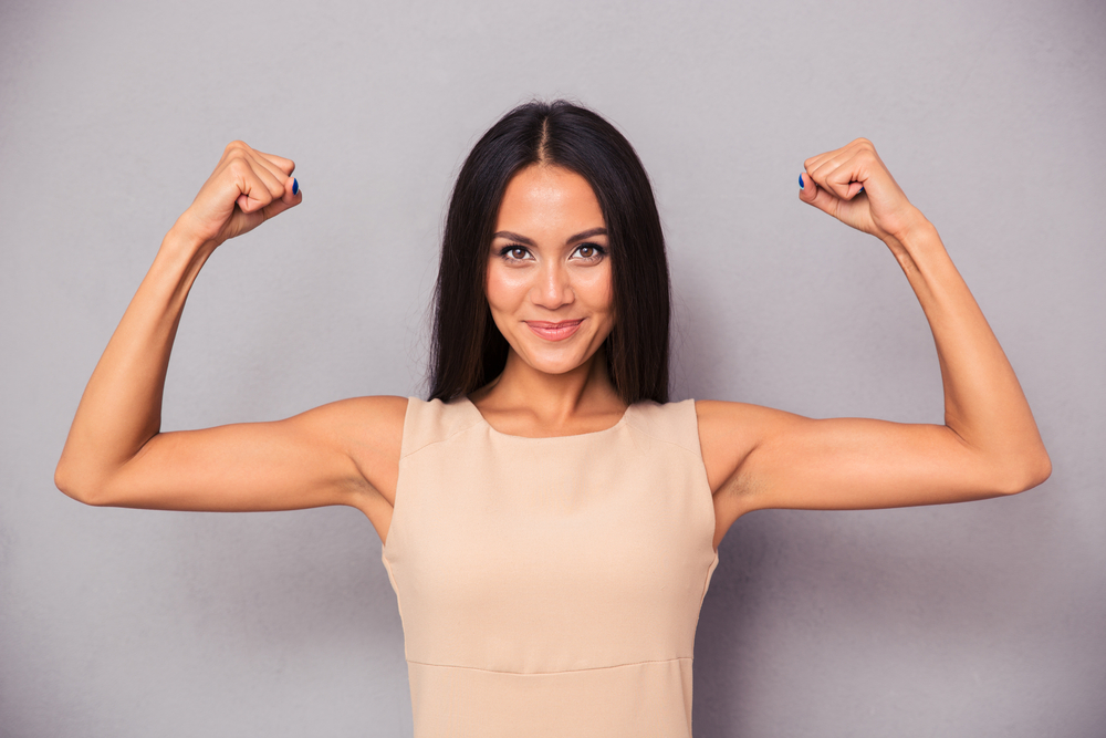 Imagine cu o femeie care își încordează brațele și zâmbește