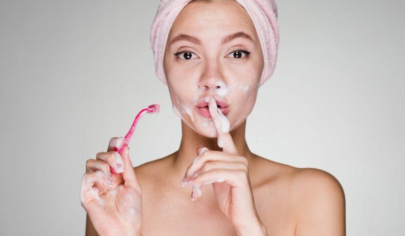 Femeie cu prosopul pe cap, dipă baie, care folosește epilarea facială