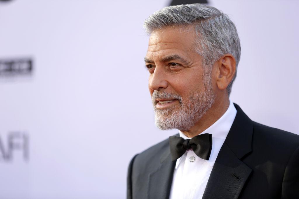 George Clooney pe covorul roșu îmbrăcat cu sacou negru, cămașă albă și papion
