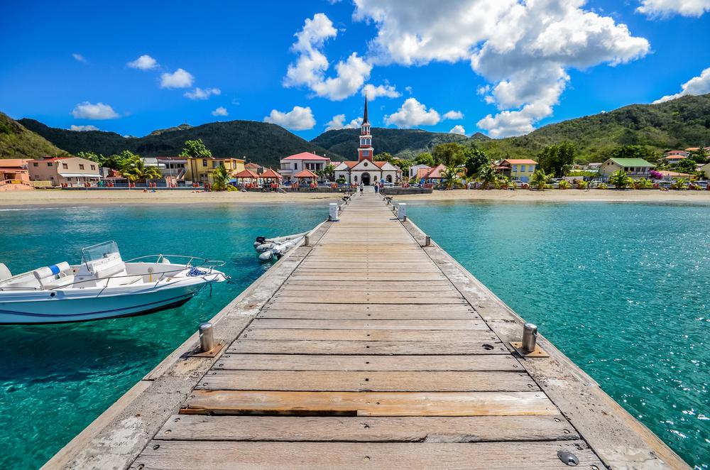 Un pod de lemn deasupra apei cristaline, lângă care se află o barcă albă cu moto