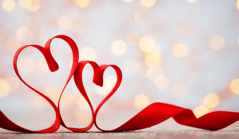 Două inimi modelate dintr-o panglica rosie