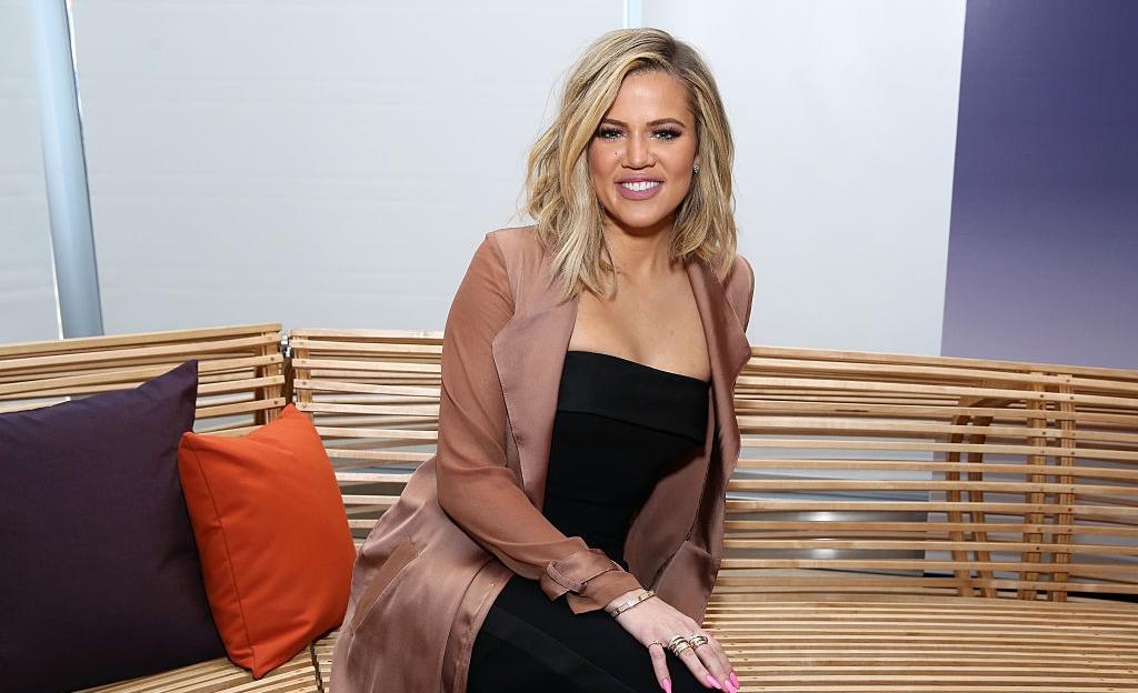 Khloe Kardashian zâmbelte și stă așezată pe o canapea îmbeăcată într-o rochie neagră mulată