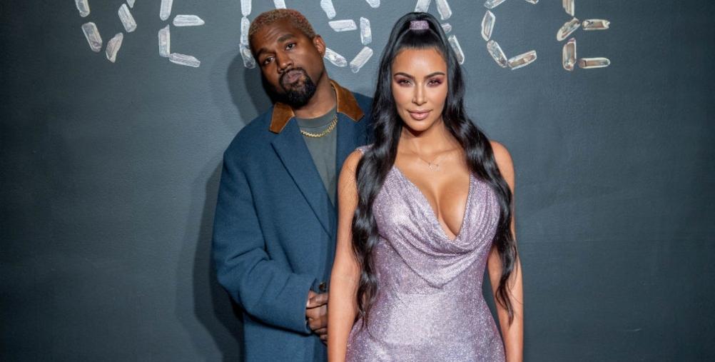Kim Kardashian îmbrăcată într-o rochie Lila alături de Kanye West pe covorul roșu la o prezentare de modă Versace