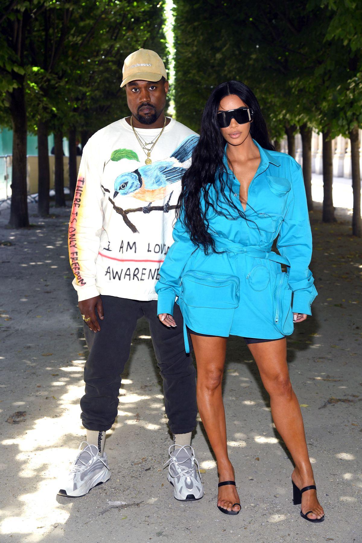 Kim Kardashian, într-o ținută turcoaz și cu ochelari supradimensionți, fotografiată alături de Kanye West la Paris Fashion Week, în anul 2018